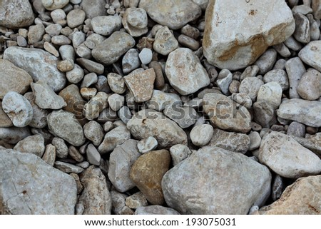 Smooth natural stones in a stream bed in subdued shadow illumination - stock photo