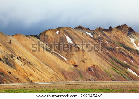 Smooth orange rhyolite mountains in Landmannalaugar nature reserve. In the hollows snow left over from last year - stock photo