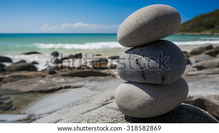 Smooth Symbolic Oval Stones Delicately Stacked On Top of Each Other Also Known As Cairn Along the Coastline on a Clear Sunny Day at Granite Bay, Noosa National Park, Noosa Heads, Queensland, Australia - stock photo
