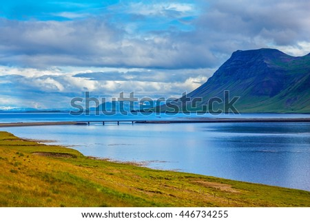 Smooth water of the cold fjord reflects clouds. Cold summer in Iceland - stock photo