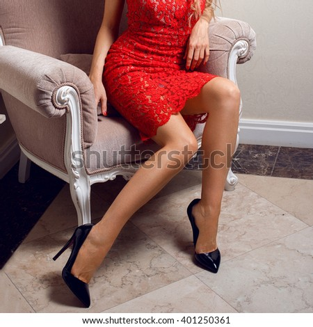 smooth woman legs in black high heel shoes and short red dress  - stock photo