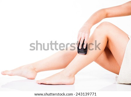 Smooth woman shaving legs with electric shaver depilator - stock photo