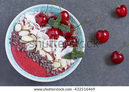 Smoothie bowl topped with cherry, coconut and almond