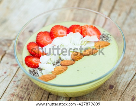 Smoothie bowl with matcha, coconut, almonds and strawberries