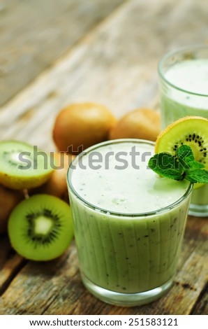 smoothie kiwi in a glass on a dark wood background. tinting. selective focus - stock photo
