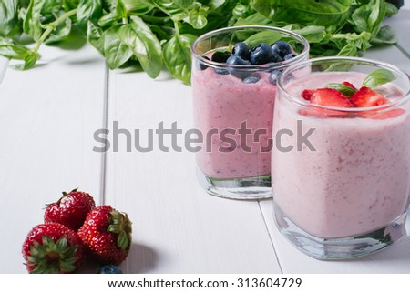 Smoothie with blueberries and strawberries on a white wooden background - stock photo