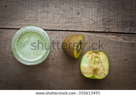 Smoothie yogurt, kiwifruit and apples in glass jar on wooden background - stock photo