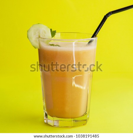 Smoothies and cucumber on the yellow background. Fresh Juice. Horizontal.