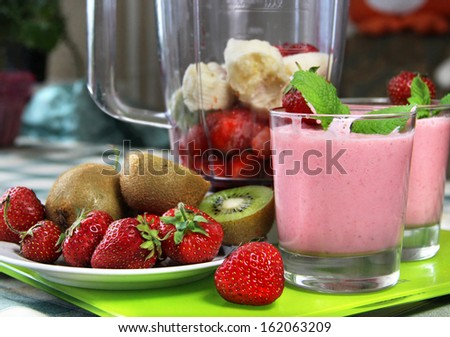 Smoothies and fresh fruits on the table - stock photo