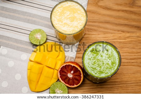 Smoothies mango and yogurt in a glass jar on wooden background.  Mango and tropical fruits  smoothies on a dark wood background