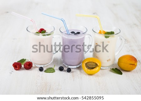 Smoothies or yogurt with fresh berries on a wooden table. Milkshakes with raspberries, blueberries, apricots and mint leaves.