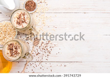 Smoothies with oatmeal, flax seeds in glass jars on a wooden background. - stock photo