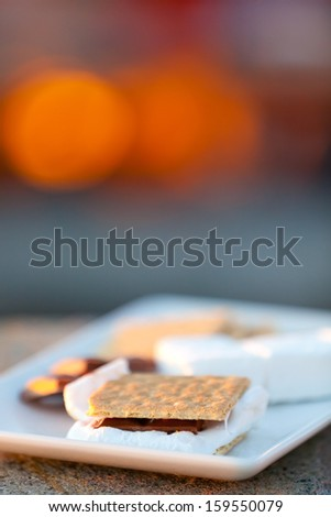 smores and its ingredients by the fire, shallow DOF - stock photo