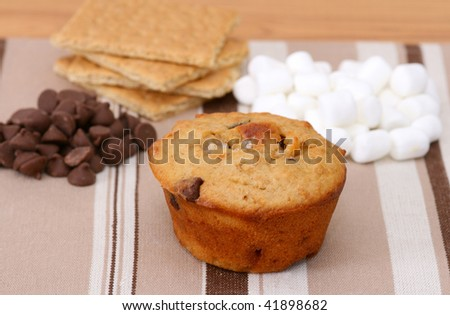 Smores muffin with chocolate chips, graham crackers and mini marshmallows on a brown striped place mat