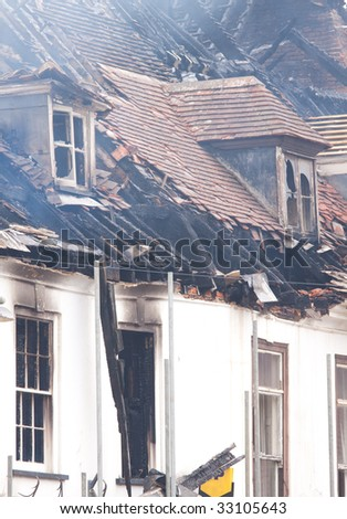 Smouldering remains of a burnt out building - stock photo