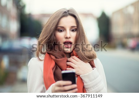 SMS. Closeup portrait funny shocked anxious scared young girl looking at phone seeing bad news photos message with disgusting emotion on face isolated cityscape background. Human reaction, expression - stock photo
