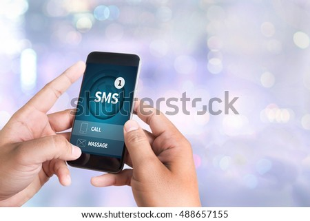 SMS Messaging Communication Notification Alert Reminder  sms person holding a smartphone on blurred cityscape background