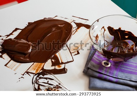 Smudging Melted Chocolate On Wooden Table - stock photo