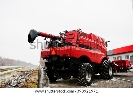 SMYKIVTSI, UKRAINE - MARCH 24, 2016: Back view of new red combine harvester at snowy weather