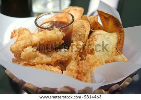 Snack basket of fried calamari and potato chips restaurant setting - stock photo