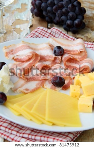 Snack cheese plate with grapes  and smoked bacon - stock photo