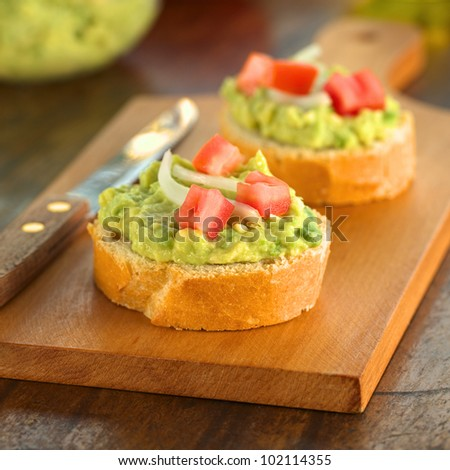Snack of baguette slices with avocado cream, tomato and onion on wooden cutting board (Selective Focus, Focus on the front of the avocado cream on the first baguette slice) - stock photo