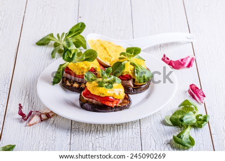 Snack of eggplant, red pepper, turkey steak, served with sauce and lettuce on a white wooden background - stock photo