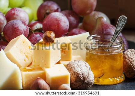 Snack plate for wine: cheese, green and pink grapes, figs, nuts and honey, selective focus