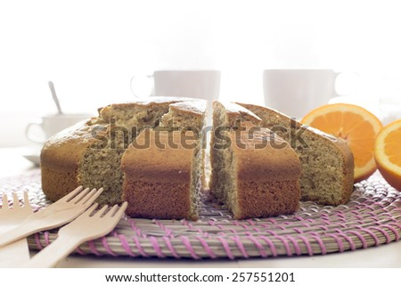 Snack with cake, tea and coffee isolated on White. Wooden table with sponge cake, icing sugar and beverages