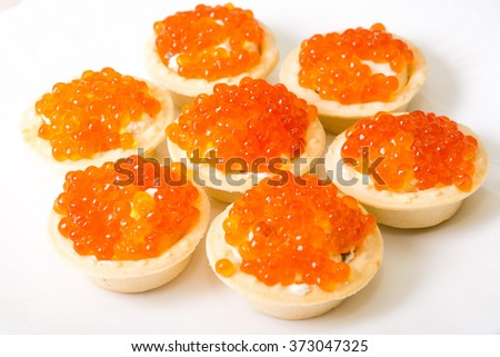 Snack with red caviar  tartlet on white plate