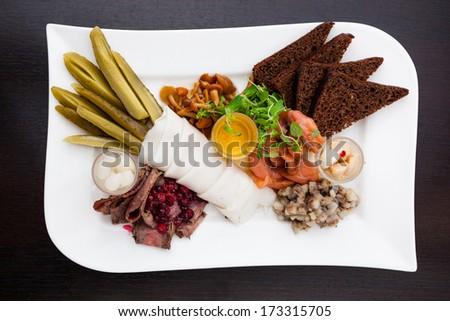 Snacks of vodka (choice of pickles, salmon, pork, roast beef, herring tartare and mushrooms) - stock photo