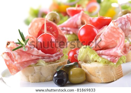Snacks with Italian salami and ripe cherry tomatoes - stock photo