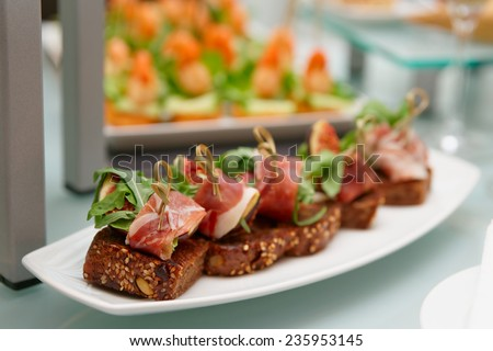 Snacks with parma ham and figs on banquet table - stock photo