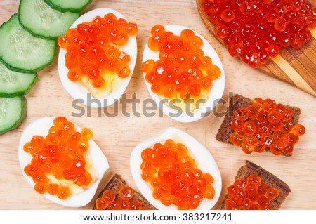 Snacks with red caviar and cucumbers - stock photo