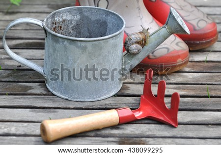snail on a small watering can with red rake and boots for children - stock photo