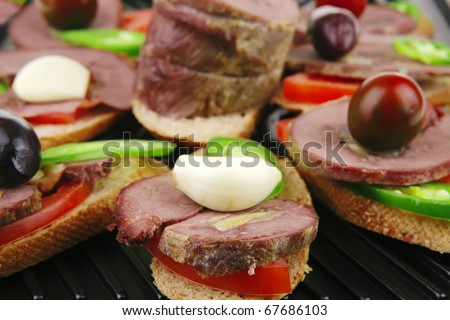 snakes on a black grill plate : meaty tartlets with supplements isolated over white background - stock photo