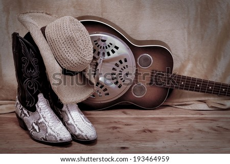 snakeskin cowboy boots with a cowboy hat propped on top in front of a dobro. Items are resting on rustic wooden surface in front of rough background. Image is desaturated and vignette added - stock photo