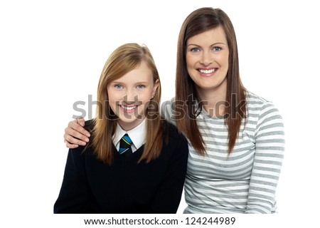 Snap shot of a mom with her arms around her cute daughter dressed in school uniform. - stock photo