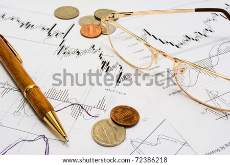 Snapshot of charts, coins, glasses and a pen. - stock photo
