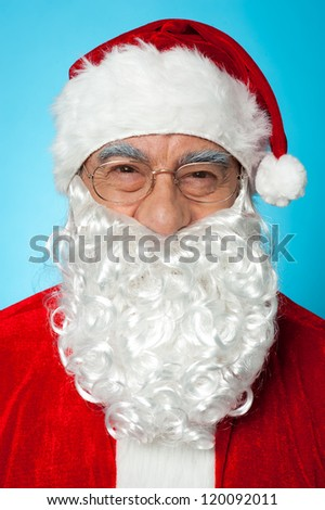 Snapshot of smiling senior man in Santa attire. Isolated on blue background. - stock photo