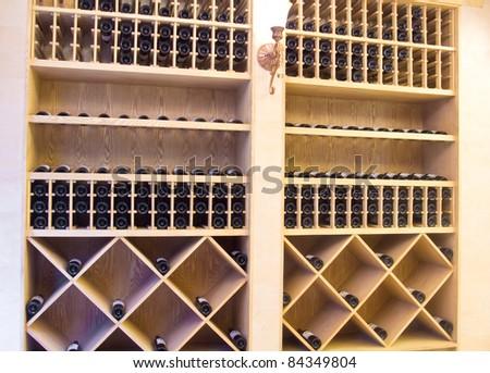 Snapshot of the wine cellar. The bottles on wooden shelves. - stock photo