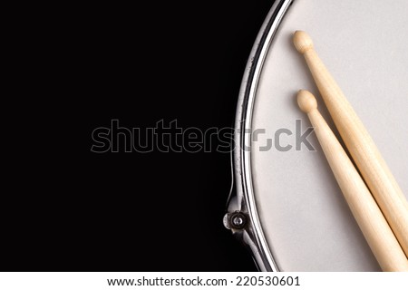 Snare drum with coated head and drumstick on black background with big copy space for text.  - stock photo