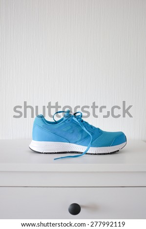 Sneaker or trainer on white commode - stock photo