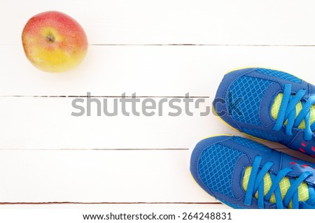 Sneakers and apple on white wooden background. Sport equipment. Selective focus - stock photo