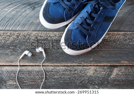 Sneakers and earphones on old wooden background top view. The image is tinted. Selective focus - stock photo