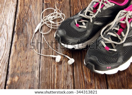 sneakers and headphones on a brown wooden background - stock photo