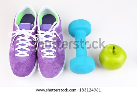 Sneakers and sport equipment. Conceptual photo of fitness progress. Isolated on white - stock photo