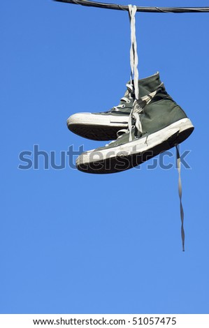 sneakers hanging from electrical wire against a blue sky - stock photo