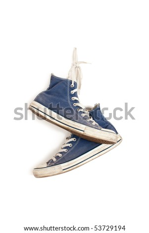 sneakers hanging on the white wall - stock photo