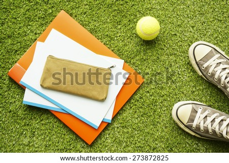Sneakers, notebooks, pen case and tennis ball on the lawn - stock photo